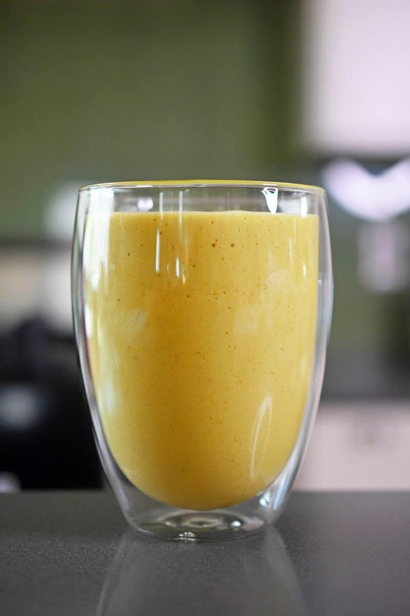 A closeup of a cup filled with paleo golden glow smoothie.