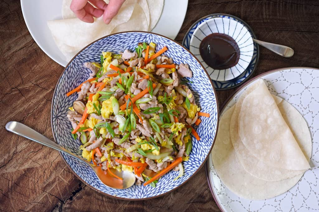 An overhead shot of Paleo Moo Shu Pork with grain-free tortillas and Paleo Hoisin Sauce.