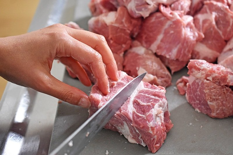 Cutting pork shoulder roast into cubes on a gray cutting board
