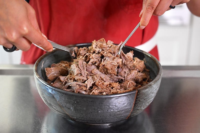 Shredding Instant Pot Magic Pork in a large bowl with two forks.