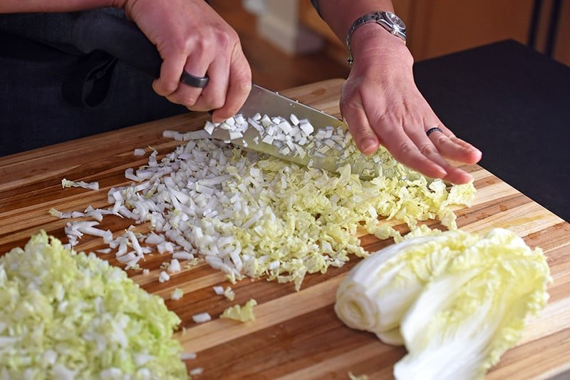 A small napa cabbage is finely chopped on a large wooden cutting board.