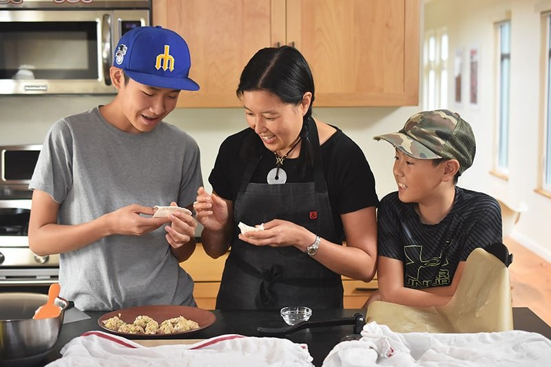 A mom and two kids are happily wrapping Paleo Pot Stickers in a brightly lit kitchen.