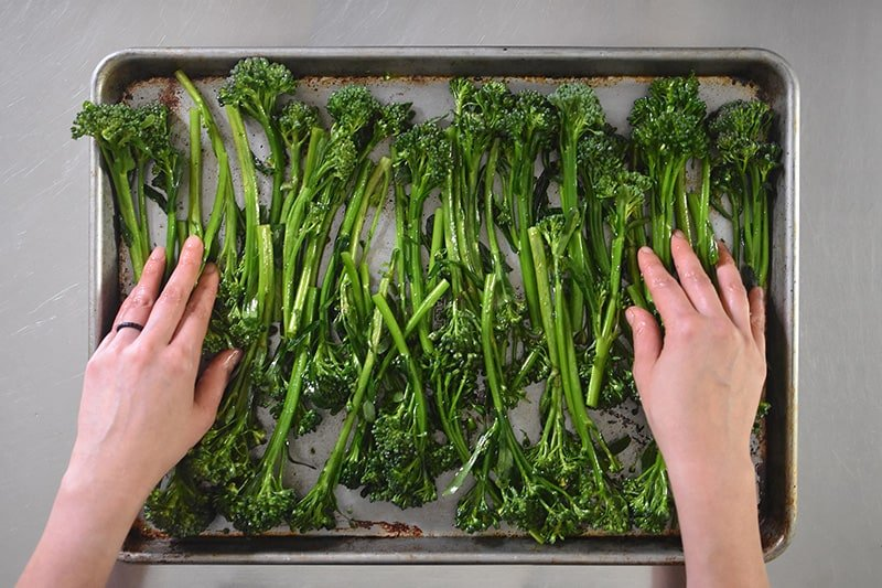 An overhead shot of seasoned broccolini on a rimmed baking sheet ready for the oven.