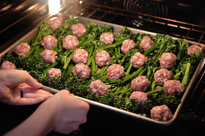 Two hands are placing a tray of Sheet Pan Meatballs and Broccolini into the oven.