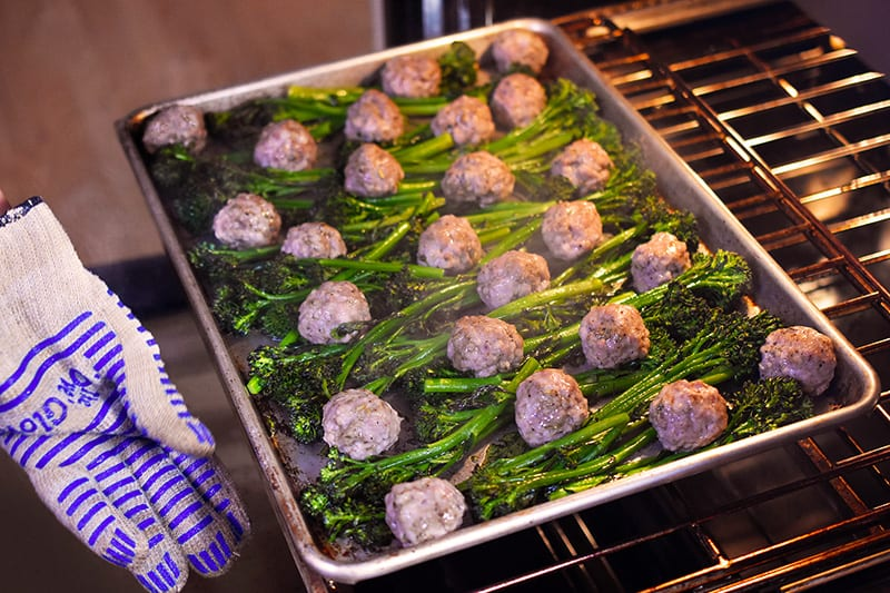 An overhead shot of someone rotating a tray of Sheet Pan Meatballs and Broccolini at the halfway point.