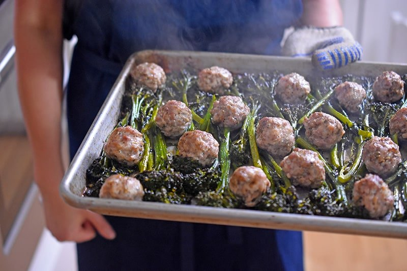 Someone carrying a steaming tray of Sheet Pan Meatballs and Broccolini.
