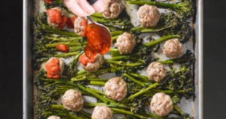 Overhead shot of Sheet Pan Meatballs and Broccolini with someone spooning marinara sauce on top.