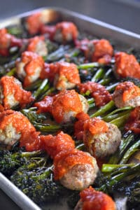 Diagonal shot of Sheet Pan Meatballs and Broccolini supper topped with marinara sauce.