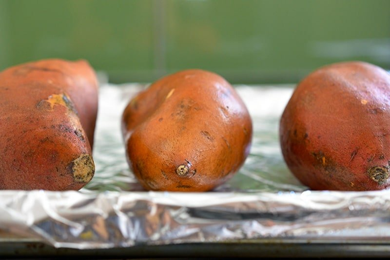Three raw sweet potatoes on a aluminum foil-lined rimmed baking sheet.