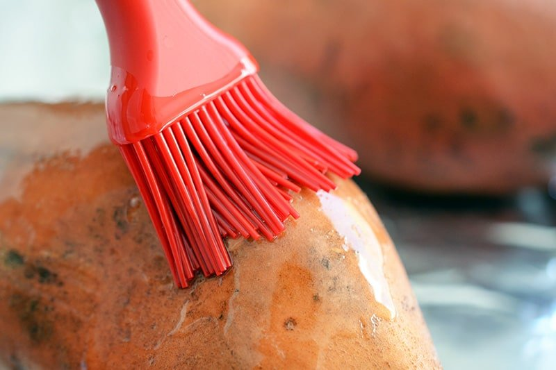 Close-up of a silicone brush applying melted fat on top of a raw sweet potato.