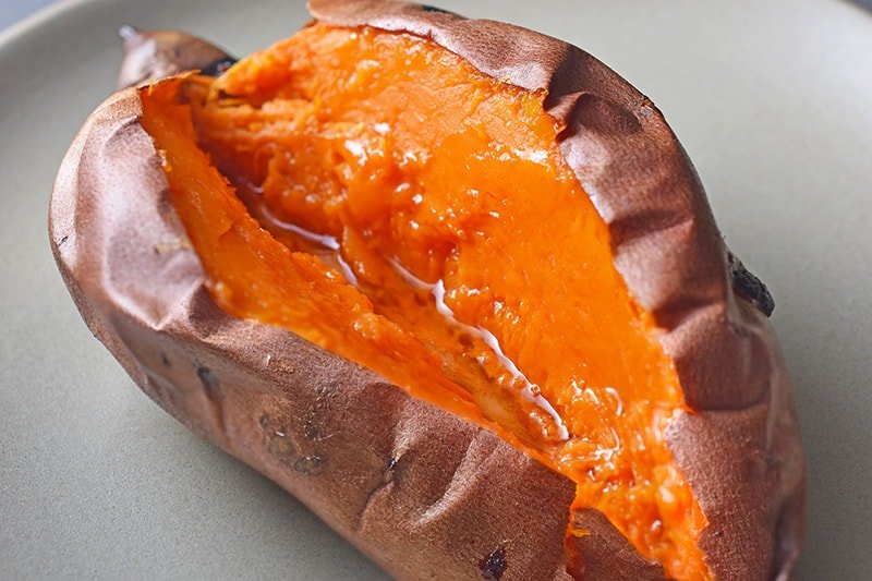 A baked sweet potato split in half with melted ghee.
