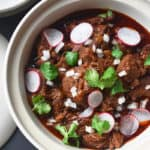 Overhead shot of Instant Pot Cowboy Chili topped with sliced radishes, cilantro, and diced onions.