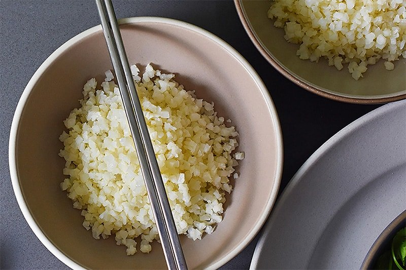An overhead shot of two bowls of simple cauliflower fried rice with a pair of silver chopsticks on top of one of the bowls.