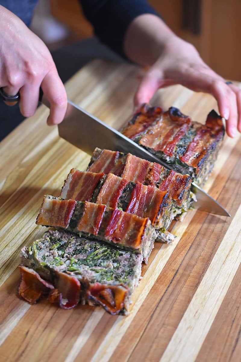 Slicing the Easy Meatloaf on a wooden cutting board.