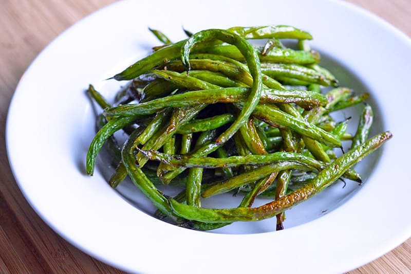 A closeup of a white plate filled with roasted green beans.