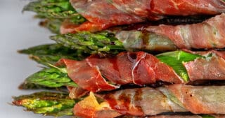 A closeup shot of broiled prosciutto-wrapped asparagus topped with aged balsamic vinegar.