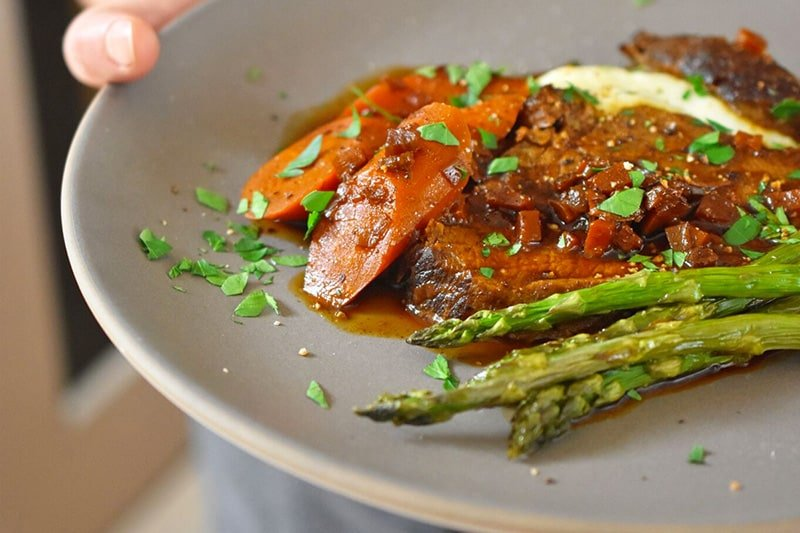 A shot of a slice of Instant Pot Yankee Pot Roast on a plate with some roasted asparagus