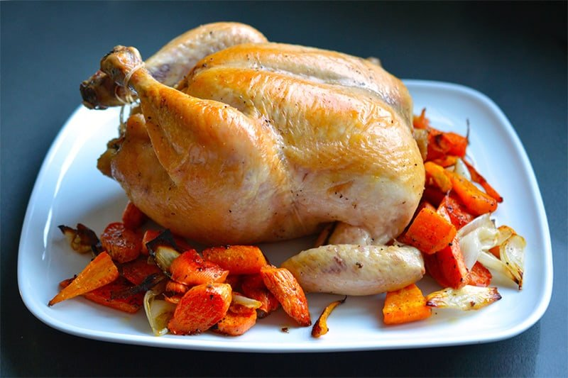 A closeup of Julia Child's Classic Roast Chicken recipe on a plate with roasted vegetables