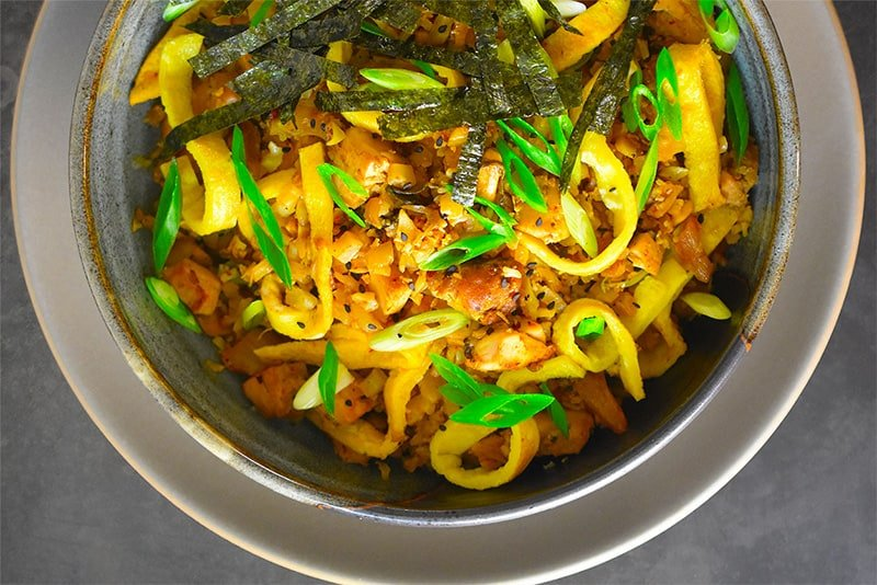 An overhead shot of a bowl of Kimchi Cauliflower Fried Rice topped with toasted seaweed slices and scallions.