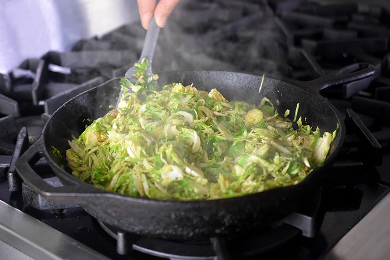 Sautéing shaved Brussels sprouts and shallots in a large cast iron skillet