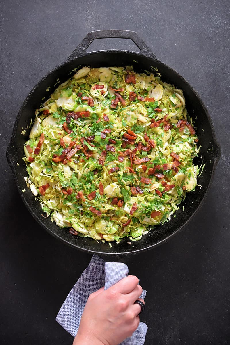 An overhead shot of a cast iron skillet filled with shaved brussels sprouts with bacon.