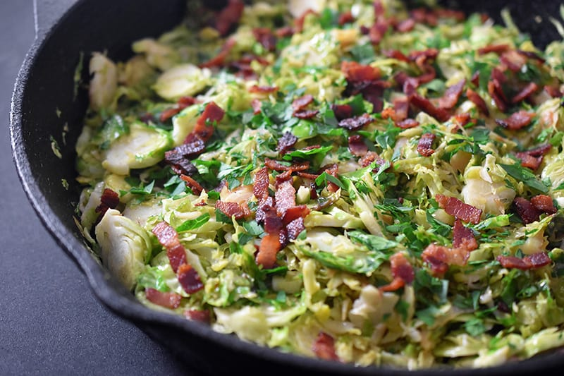 A closeup of shaved brussels sprouts and bacon in a cast iron skillet ready to serve.