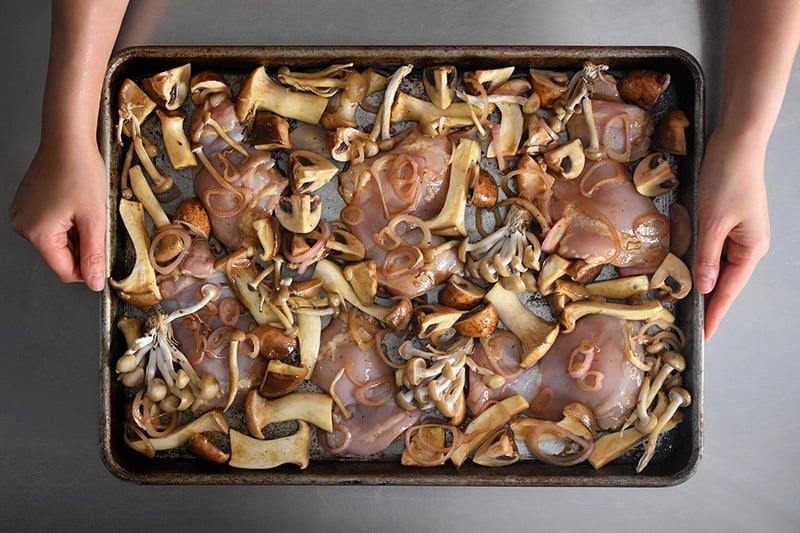 The Sheet Pan Chicken and Mushrooms should be arranged in a single layer before baking.