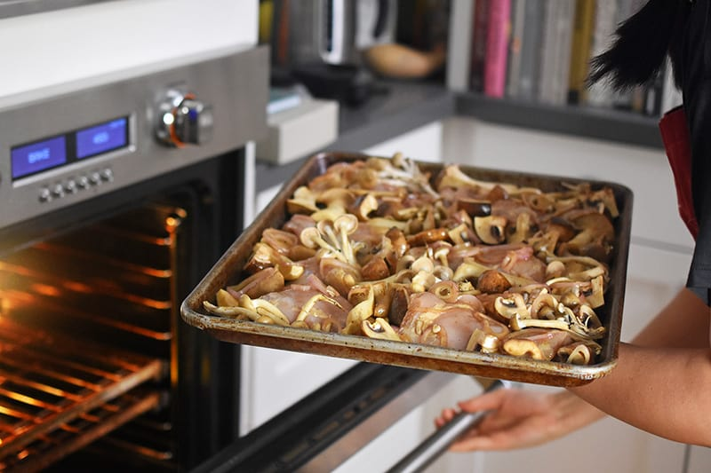 Pop the tray of Sheet Pan Chicken and Mushrooms into a hot oven.