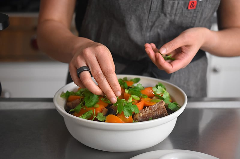 A person is adding cilantro and chopped scallions to the top of a bowl of Instant Pot Vietnamese Pork Stew.