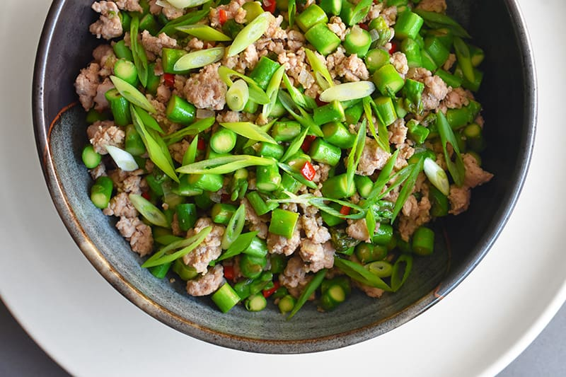 An overhead shot of Spicy Pork and Asparagus Stir-Fry in a bowl.