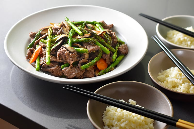 A side view of Asparagus Beef Stir-Fry in a cream serving bowl surrounded by bowls of cauliflower rice.