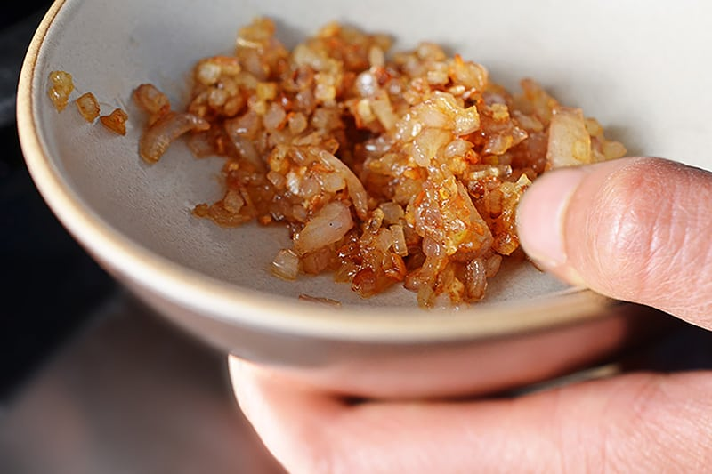 A hand holding a shallow bowl filled with caramelized diced shallots.