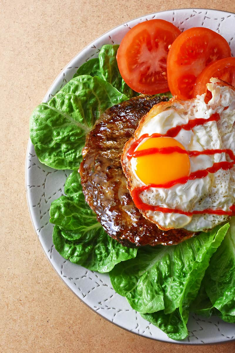 An overhead shot of a Nomster Burger on a bed of lettuce and topped with a crispy fried egg, sriracha, and sliced tomatoes.