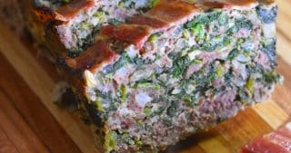 A closeup shot of sliced Easy Paleo Meatloaf on a wooden cutting board.