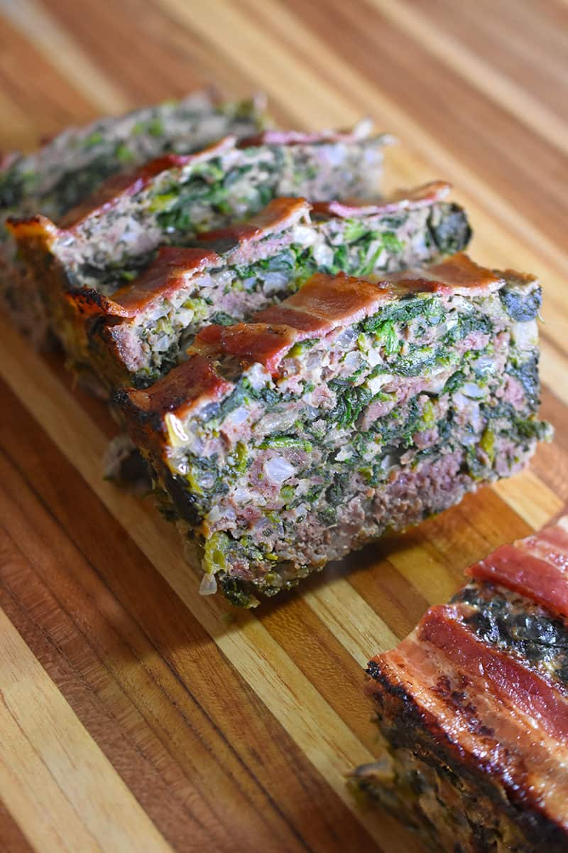 Closeup of Easy Meatloaf sliced and ready to serve on a wooden cutting board.