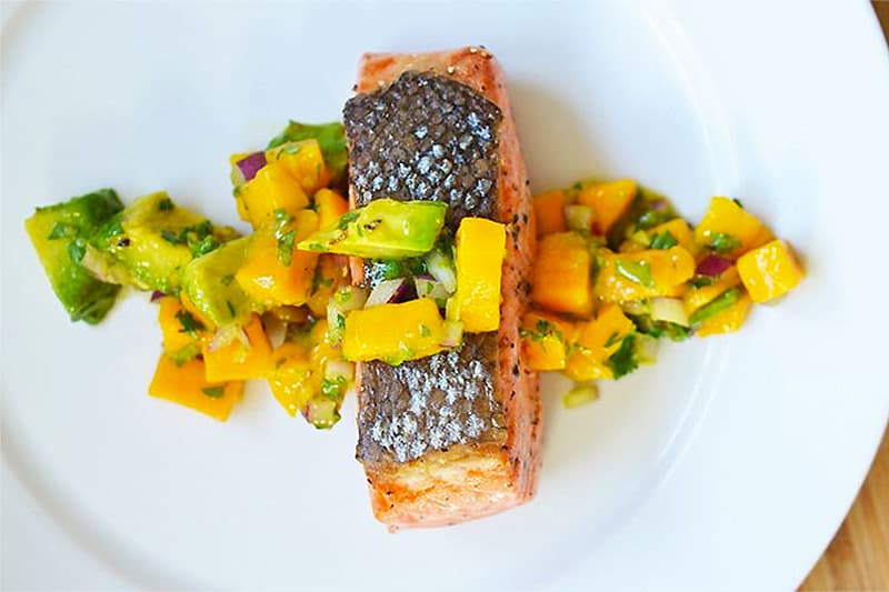 An overhead shot of Mango + Avocado Salsa on Pan-Seared Salmon