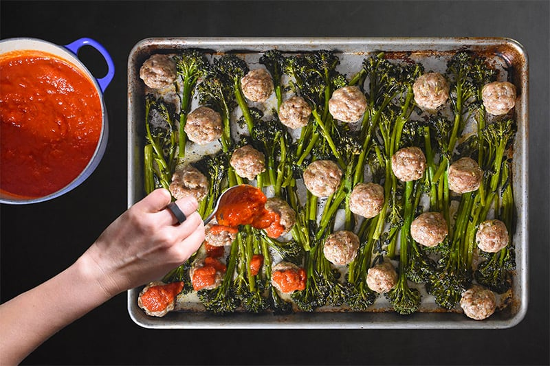 An overhead shot of someone spooning marinara sauce on Sheet Pan Meatballs and Broccolini