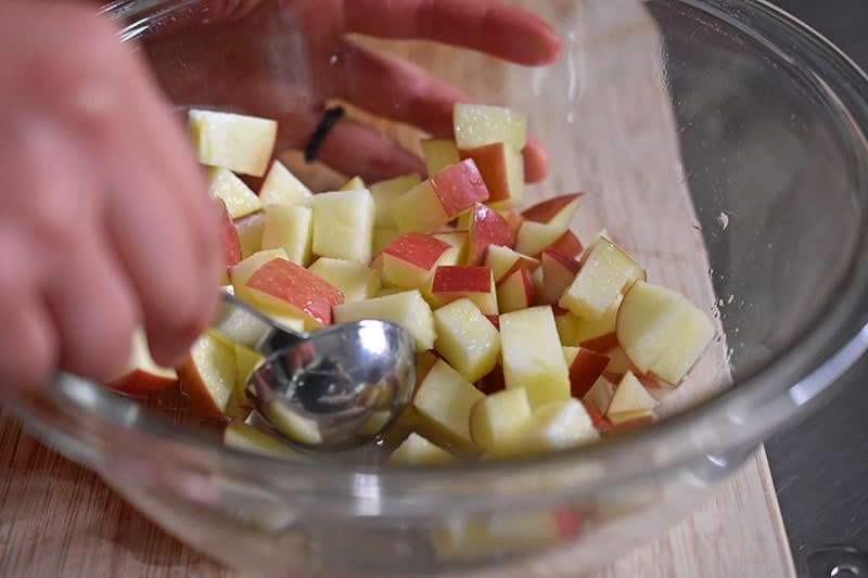 Stirring the apple cubes with lemon juice in a glass bowl