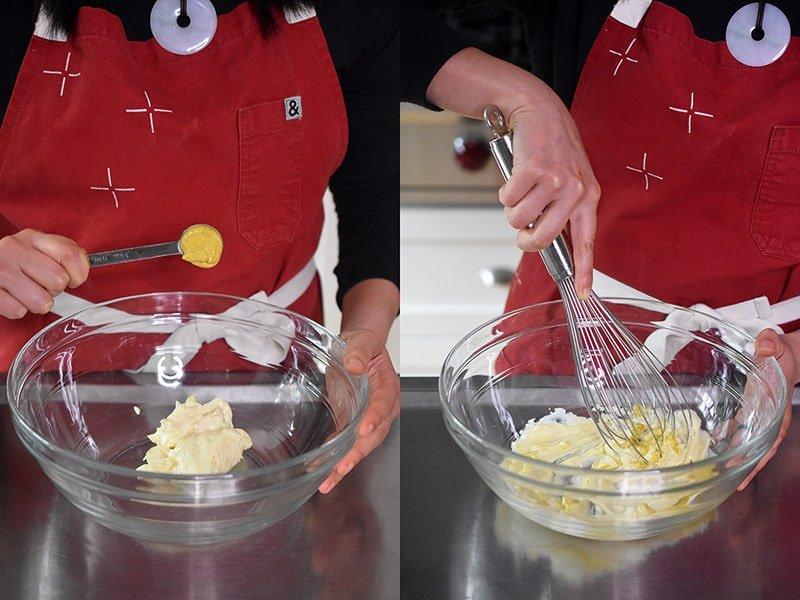 Whisking mayonnaise and Dijon mustard in a large glass bowl