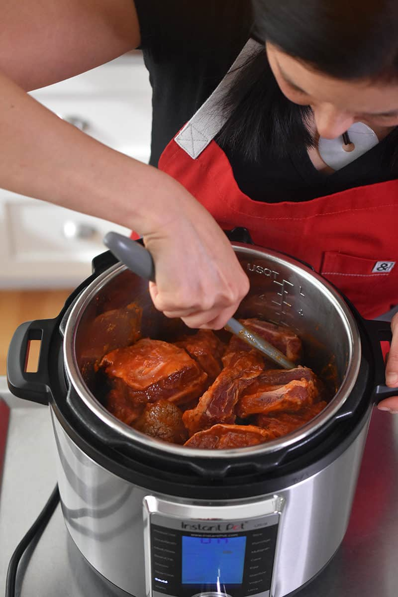 An overhead shot of someone stirring the Instant Pot Magic Short Ribs with a gray silicone spatula to combine all the ingredients.