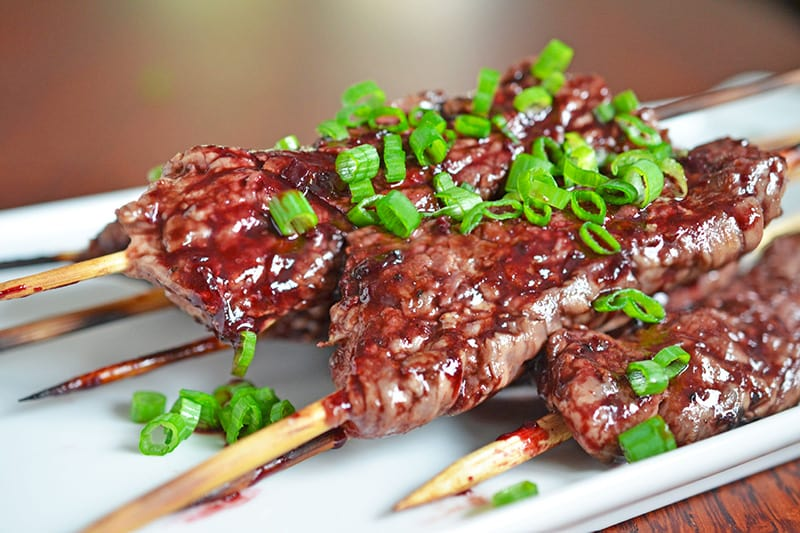 A dish filled with Smashed Steak Skewers topped with Whole30 cherry BBQ sauce and sliced scallions.