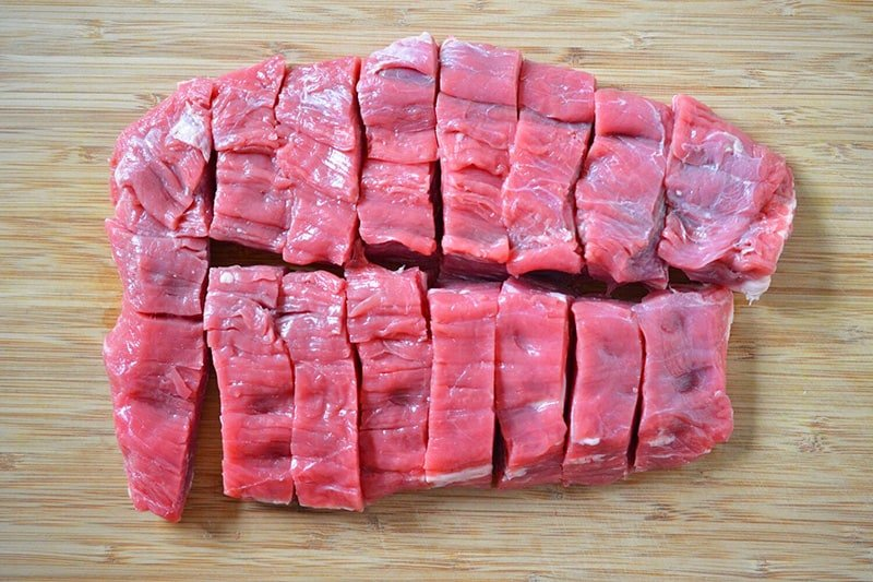 The piece of flank steak is shown cut into 16 even pieces