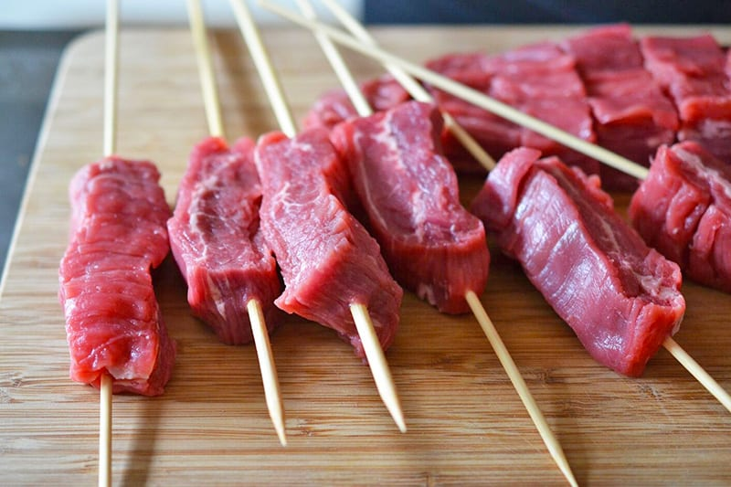 A wooden cutting board has a bunch of flank steak kabobs waiting for the barbecue.