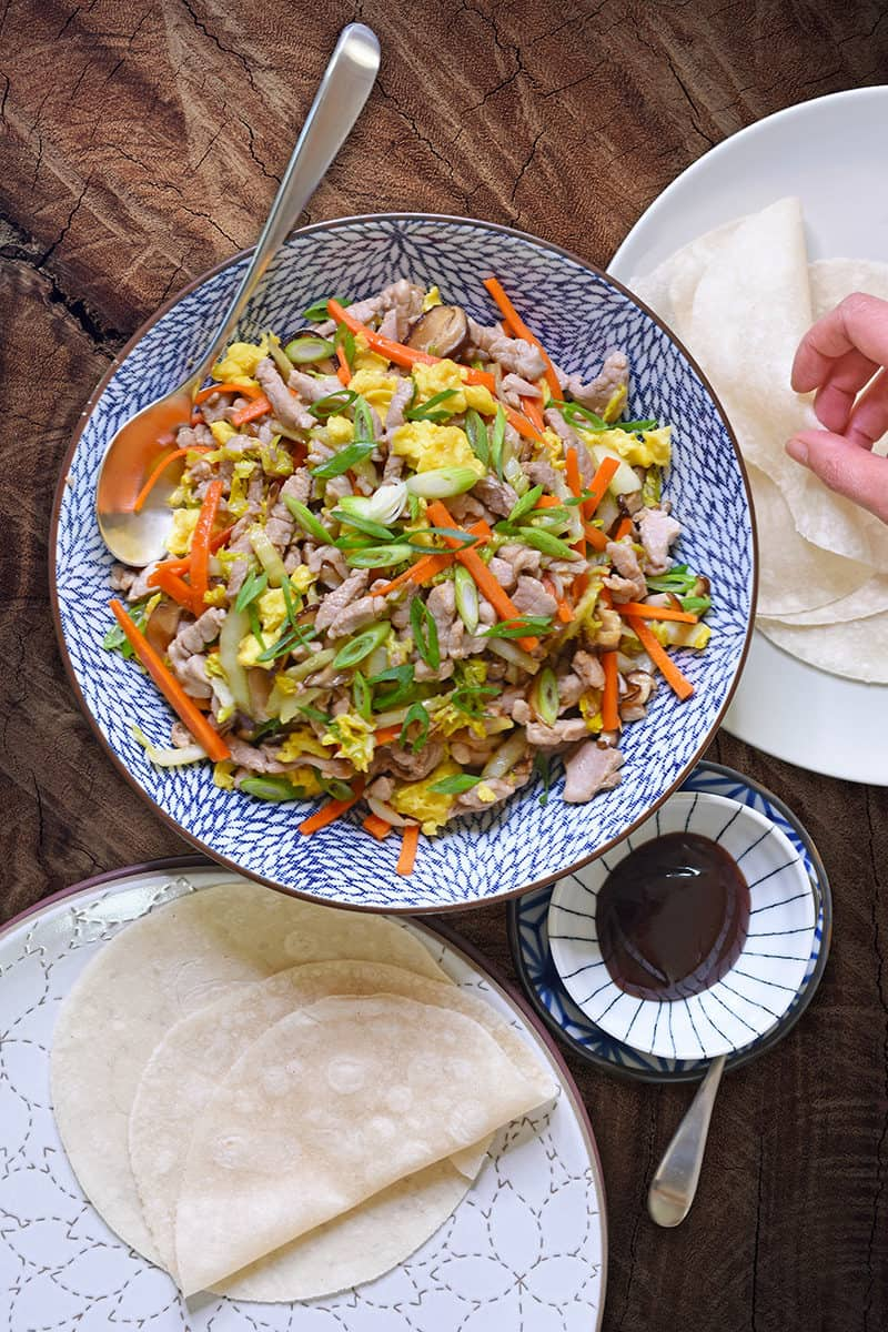 An overhead shot of a serving bowl filled with Paleo Moo Shu Pork, along with grain-free tortillas, and paleo hoisin sauce.