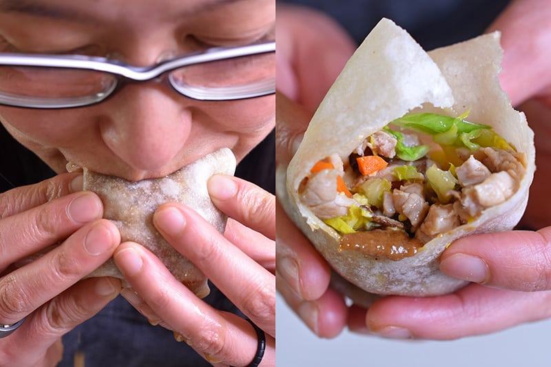 On the left, a woman with glasses is biting into a grain-free tortilla filled with Paleo Moo Shu Pork. On the right, is a shot of the inside of the Paleo Moo Shu Pork after a big bite has been taken.