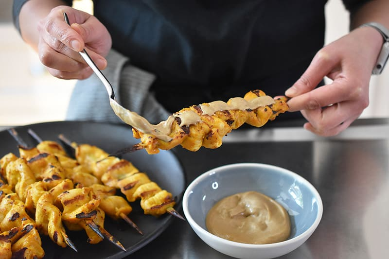 Someone spooning Hoisin No-Nut Sauce on Chicken Satay skewers.