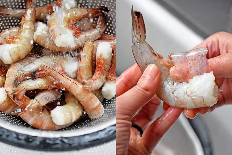 Frozen jumbo shrimp in a colander being rinsed with water. On the right, someone is peeling the shell off a shrimp.