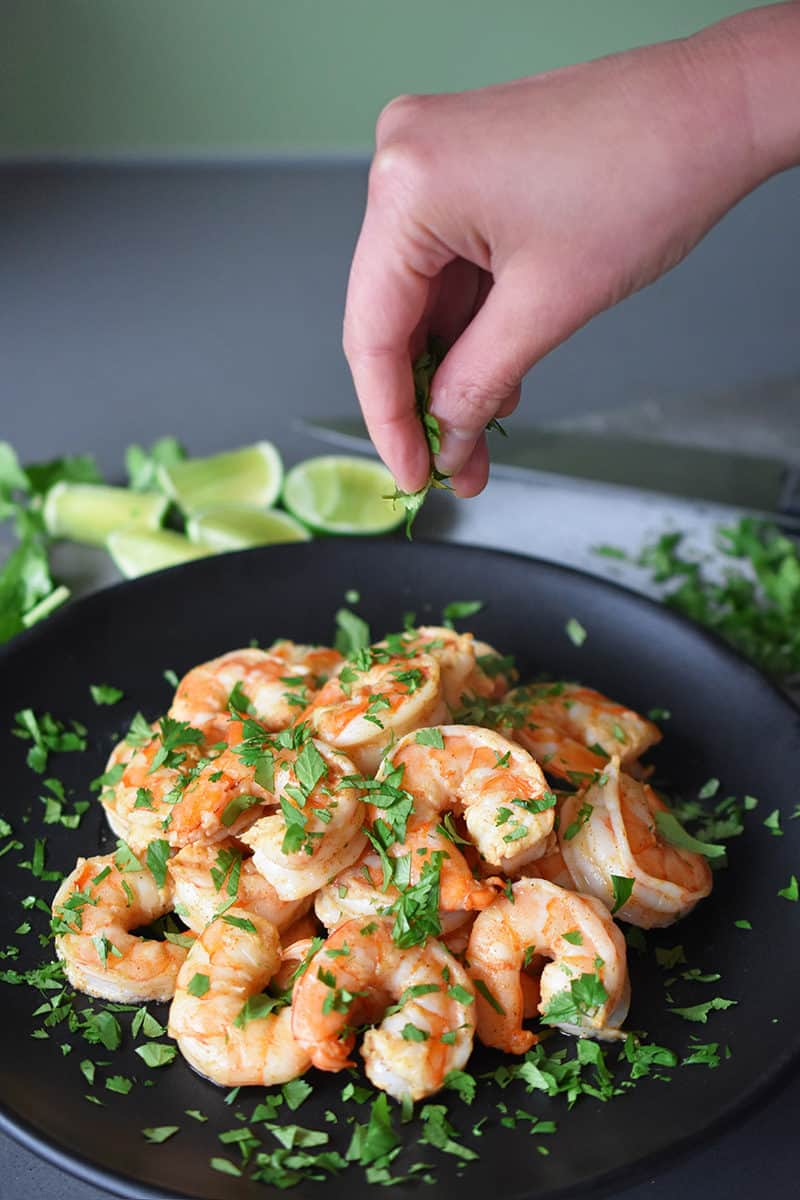 Sprinkling minced fresh cilantro leaves on top of a platter of Tandoori Shrimp.