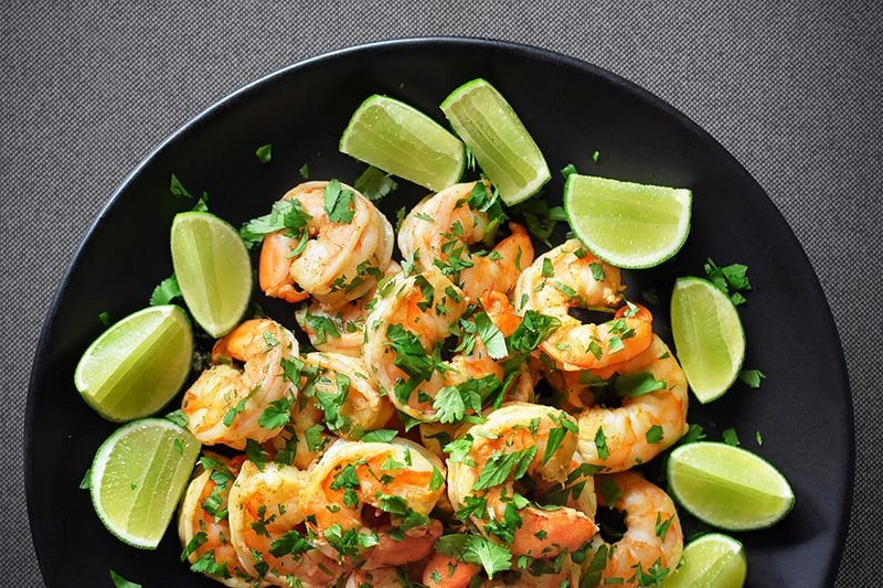 An overhead shot of Tandoori Shrimp on a black platter, surrounded by lime wedges.