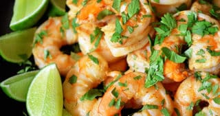 A side shot of Tandoori Shrimp on a black platter with lime wedges on the side.